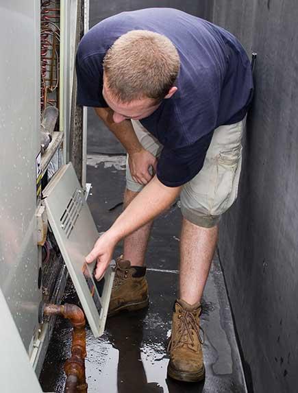 HVAC technician opens a commercial condenser unit