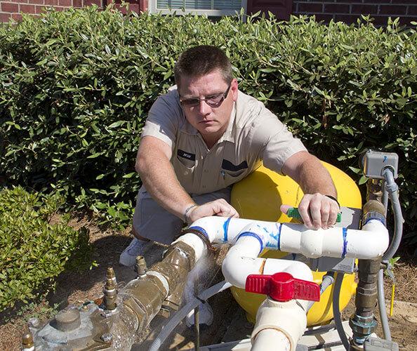 plumber clears backflow device